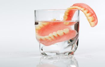 Set of Dentures in Glass of Water